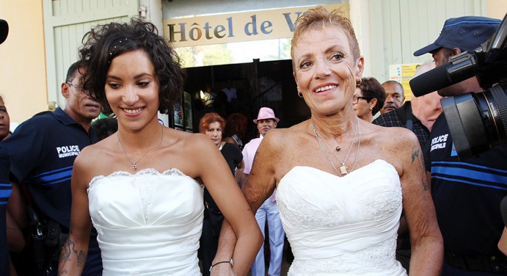 Corinne Denis (R) and Laurence Cerveaux (L) celebrate after being declared married  at Saint-Paul de la Reunion city hall during the first official gay marriage French island of La Reunion. France is the 14th country to legalise same-sex marriage, an issue that has also divided opinion in many other nations. The definitive vote in the French parliament came on April 23 when the law was passed legalising both homosexual marriages and adoptions by gay couples. / AFP / RICHARD BOUHET